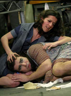 Salud (Mary Plazas) mutually comforts the transvestite worker (Richard Coxon). Photograph by Stephen Vaughan.